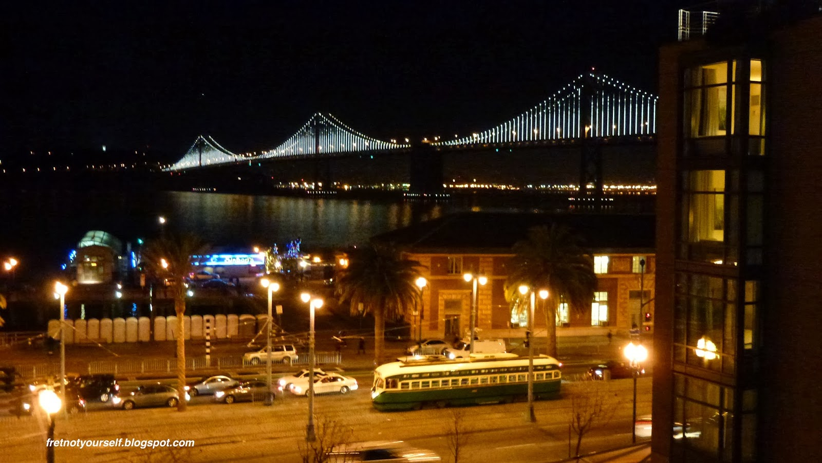 The LED lights on the cables and supports glow against the dark sky and waters of San Francisco Bay. A yellow and green streetcar passes along Embarcadero Street in the foreground.