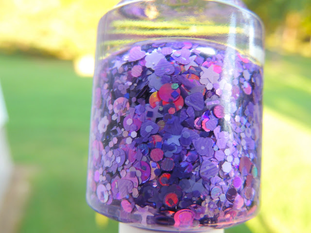 FEAR- a clear based filled with purple flowers, purple stars, purple hearts, large holo purple dots, purple shreds, purple squares, and tons of purple micro glitter.