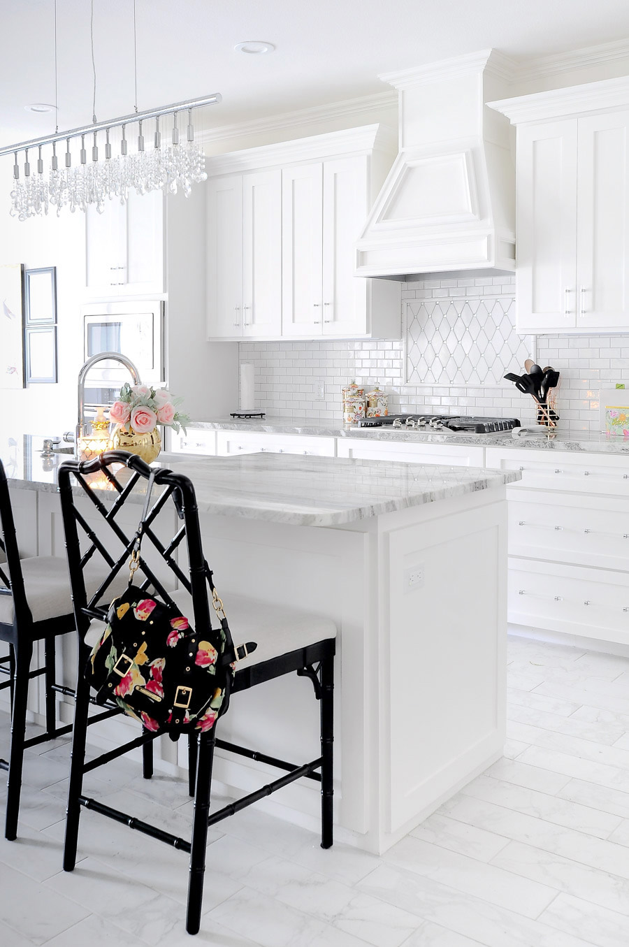 Bright white shaker cabinet kitchen with marble backsplash, gray countertops, and black bamboo counterstools.