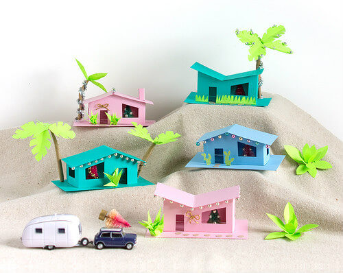 Five mid-century ranch houses made of paper with holiday decorations, palm trees, car and trailer