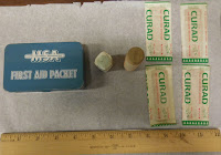 "Small box marked ""MSA First Aid Packet,"" 2 cylindrical containers, and 4 Curad brand bandaids"