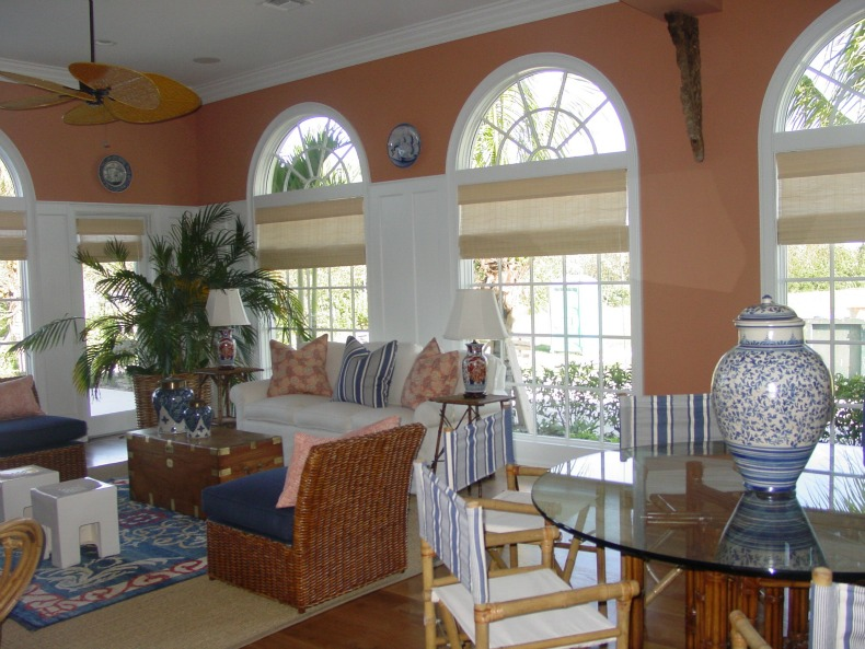 coral coastal family room with white sofa and wicker slipper chairs