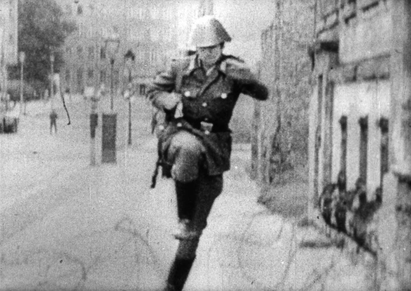 Schumann tossed aside his cigarette, then turned and ran for the coil of barbed wire that marked the boundary between East and West. (Still from the video footage).