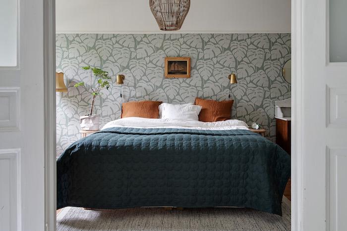 Dormitorio con cabecero forrado con papel pintado a media altura