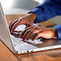 man's hands typing on laptop