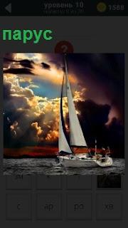 Яхта в свете заката под парусом плывет по волнам в свете вечернего заката с еле пробиваемого луча солнца