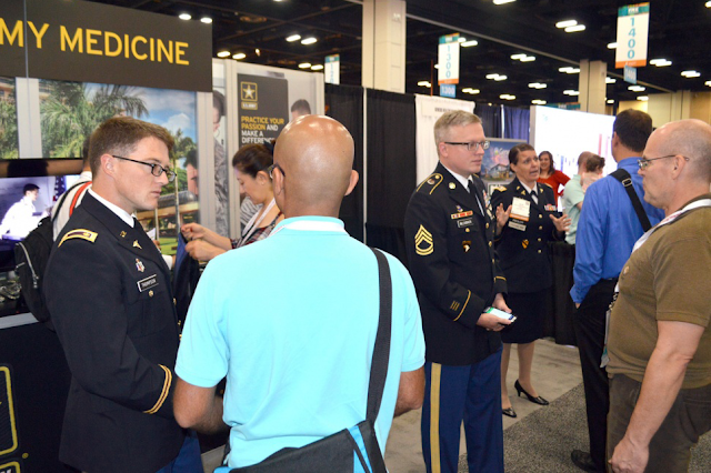 people in military uniform talk to civilians at a information fair