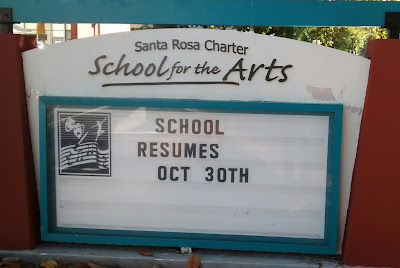 Display sign in front of exterior, Santa Rosa Charter School for the Arts. Lettering inside a glass case states, 'School resumes Oct 30th'
