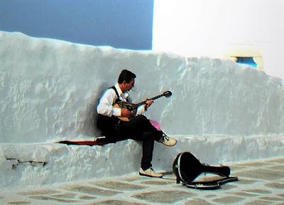 Mężczyzna ubrany w białą koszulę i czarne spodnie siedzi na białym murze na ulicy Mykonso w słoneczny dzień gra na buzuki