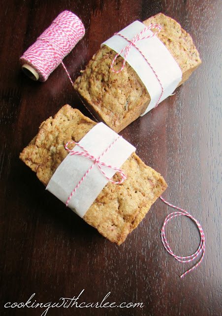two small loaves of bread wrapped in parchment paper and bakers twine