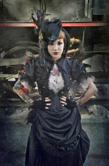 Woman with colorful tattoos standing in front of a steam train wearing steampunk clothing. She wears a black dress, corset, white lace blouse, hat and fingerless gloves.