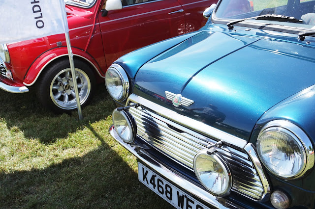 a metallic blue classic mini cooper next to a red one