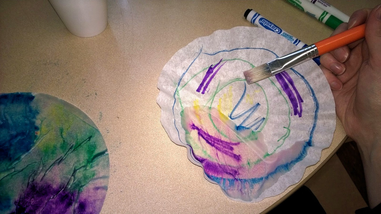 "Dip paint brush in water and paint over the coffee filters, watching the colors ""run."""