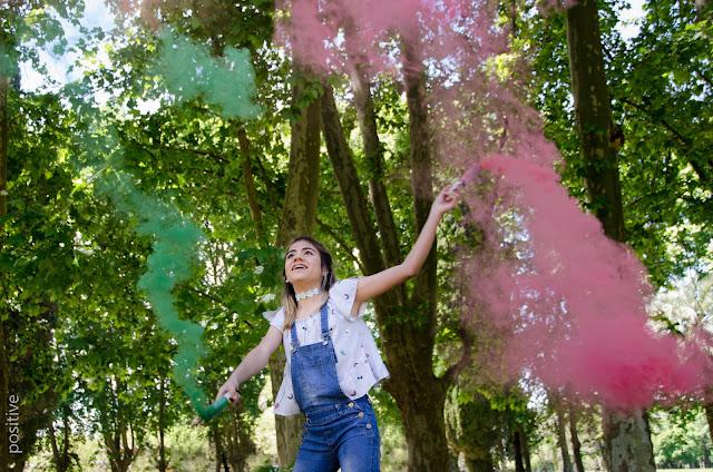Chica de 15 años con bengalas de humo de colores en el bosque