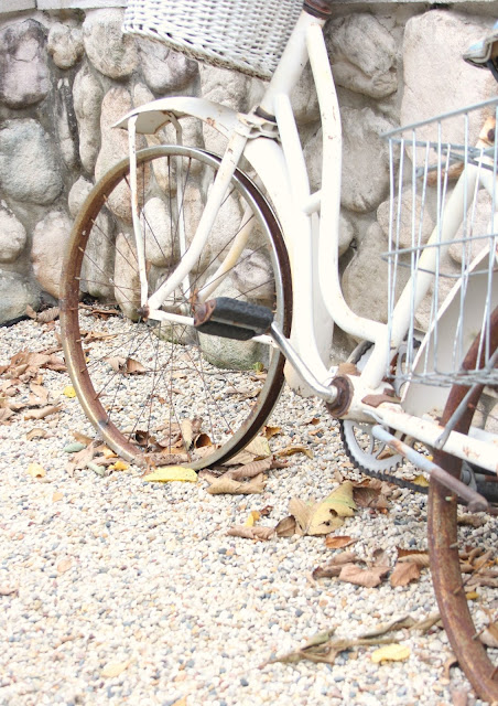 Vintage rusty white bicycle against stone wall in pea gravel and fallen leaves by Hello Lovely Studio