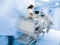 Ziekenhuis bed met apparatuur wordt door een ziekenhuis gereden