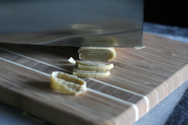 Close-up of knife about to slice through rolled up ramen noodle dough. The rolled up ramen noodle dough has a spiral of flour.