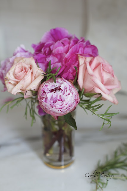 Roses and peonies with rosemary in glass vase