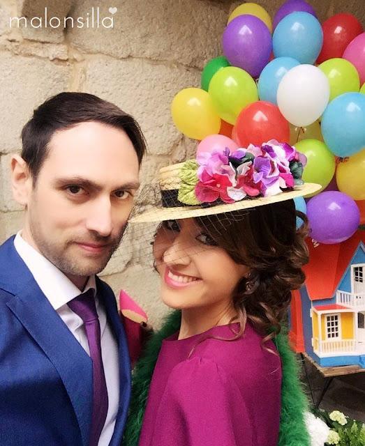 Invitada de boda decorada como pelicula UP de Disney, con vestido de Asos berenjena, estola de pelo verde botella y canotier de flores en negro y berenjena con velo