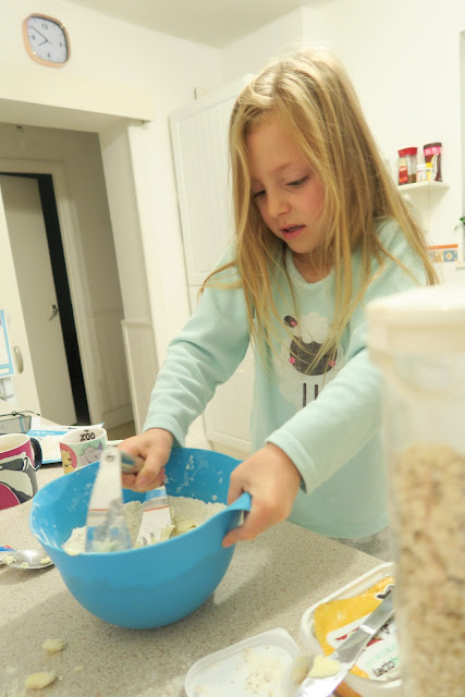 Lily standing at the kitchen counter, using a metal pastry cutter to make a crumble topping using flour, oats, butter and sugar.