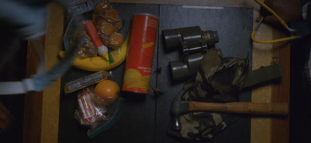 en una mesa caen de una mochila gris, numerosas chuches, también hay en la mesa un martillo, unos prismáticos y un pañuelo verde con estampado militar