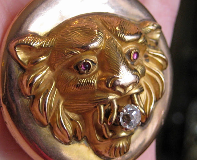 An antique lion-headed pendant in gold with diamonds and rubies. Victorian era.