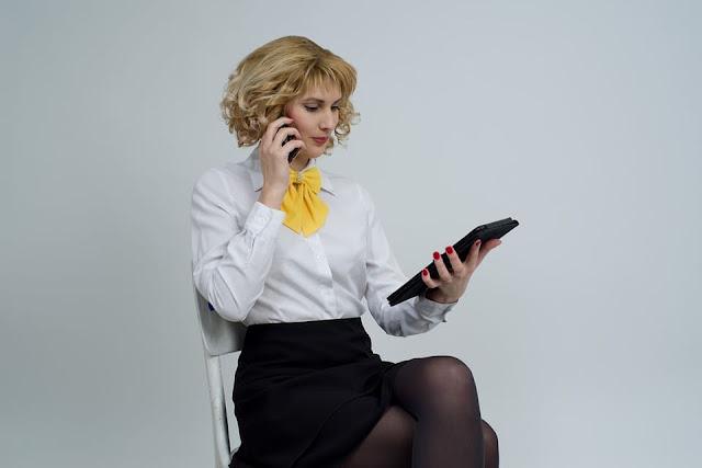 Mulher usando tablet e celular para trabalhar