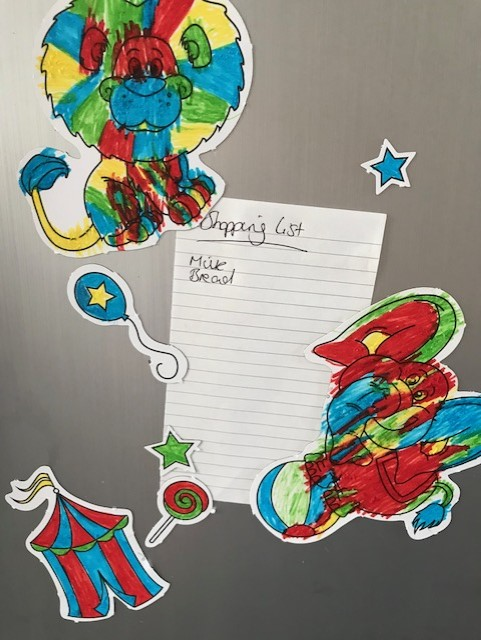Shopping list held on a fridge by a variety of circus themed magnets coloured in rainbow colours