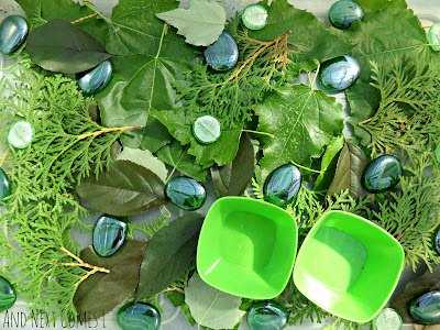 Close up of green themed sensory bin from And Next Comes L