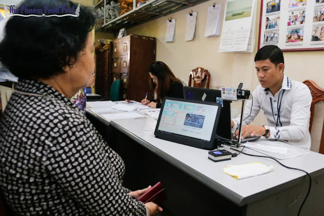An official processes a person's identification card at a voter registration office in Phnom Penh last month. Pha Lina