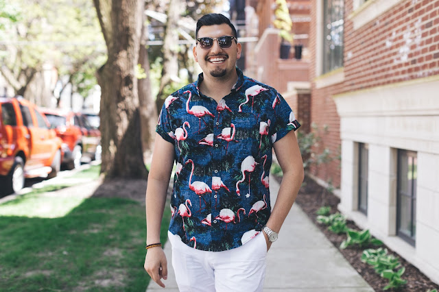 A man wearing a flamingo floral t-shirt with white pants and loafers.