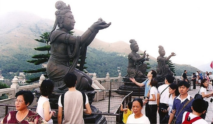 Buddhistic statues praising and making offerings to the Tian Tan Buddha.