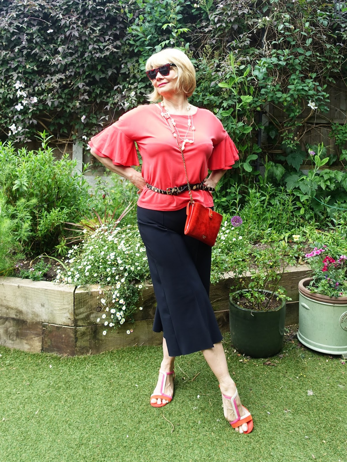 Woman wearing red top with statement sleeves and black cropped trousers
