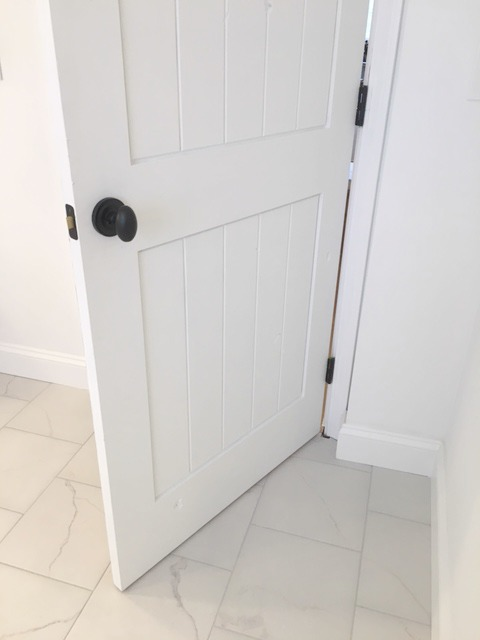 White painted knotty alder door in master bathroom renovation of Hello Lovely Studio