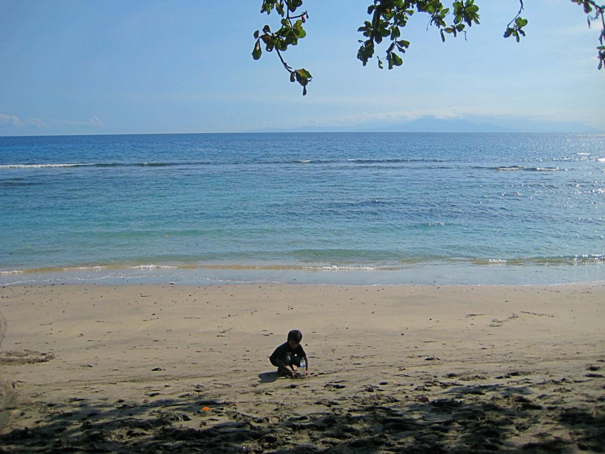 한적한 해변에서 모래놀이를 하는 아이