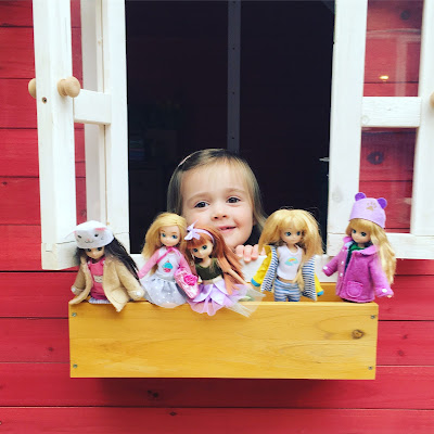 Phoebe playing with her lottie dolls in the playhouse outside