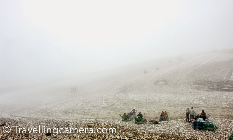 It was very foggy and we could hardly see beyond the road. As we got down from our car, there were lot of kiosks to rent out snow gears. Before taking any decision, we planned to get climb to the area where lot of tourists were having fun on snow scooters. The snow was very dirty as you can see in these photographs. Because this was not fresh snow and this road becomes very busy during summers, all the dust settles down on white snow and the whole space looks very dirty.  In fact, this is the time when snow is hard. It was very disappointing for us, but we were happy that we would be seeing snow on next terrains where tourist cars hardly go to make these white landscapes dirty.
