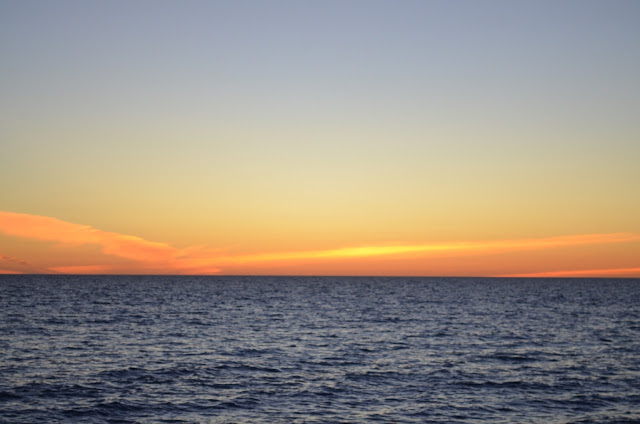 Sunset over water: deep blue water in the foreground. The horizon  is met by pink, orange and yellow clouds which clear to a darkening blue sky at the top of the photo