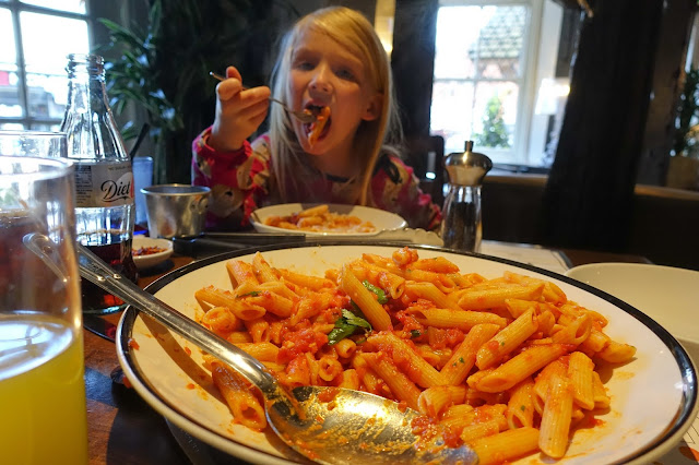 A large bowl of arrabbiata pasta in Prezzo with a young girl eating the pasta in the background