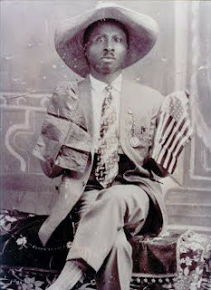 Prophet Noble Drew Ali seated wearing a sombrero hat holding the US and Moorish flags in his right and left hands.