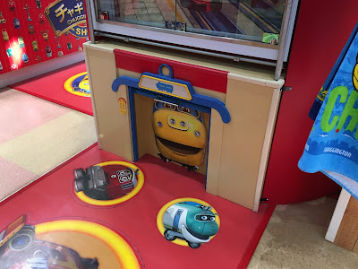 Brewster hiding behind a cabinet door at the Chuggington Shop