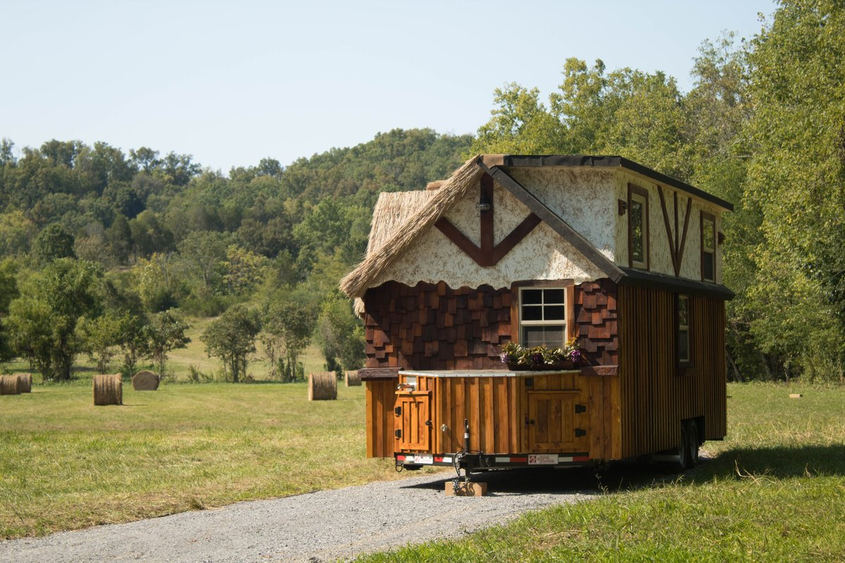 11-Exterior-View-The-Highland-Tiny-Home-on-wheels-with-Thatched-Roof-www-designstack-co