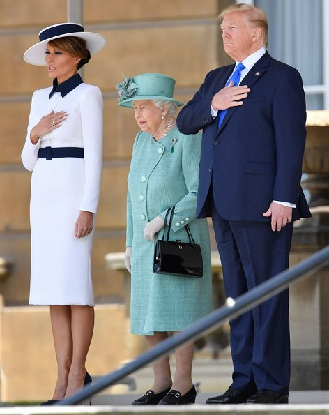 Melania Trump is wearing a custom white crepe dress with navy details by Italian fashion house, Dolce & Gabbana. Queen Elizabeth