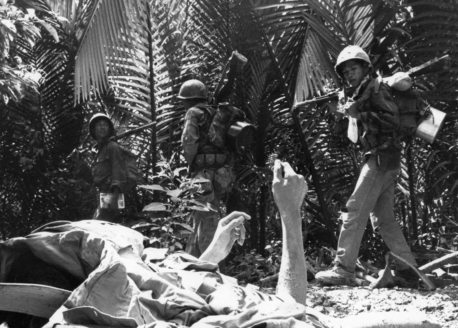 Partially covered, a dying Viet Cong guerrilla raises his hands as South Vietnamese Marines search palm groves near Long Binh in the Mekong Delta, on February 27, 1964. The guerrilla died in a foxhole following a battle between a battalion of South Vietnamese Marines and a unit of Viet Cong.