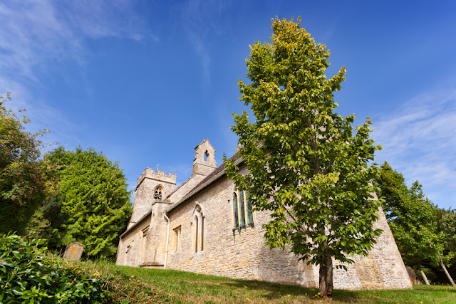 Saint Nicholas church under blue sky at Asthall by Martyn Ferry Photography