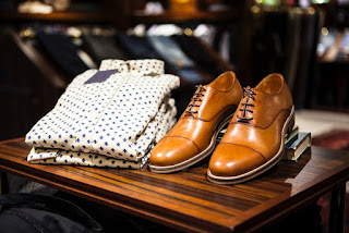 A stack of neatly folded white shirts with a small black spotted design covering the shirts next to a pair of light brown thick suede brogues on a dark brown rectangular coffee table on a dark background.