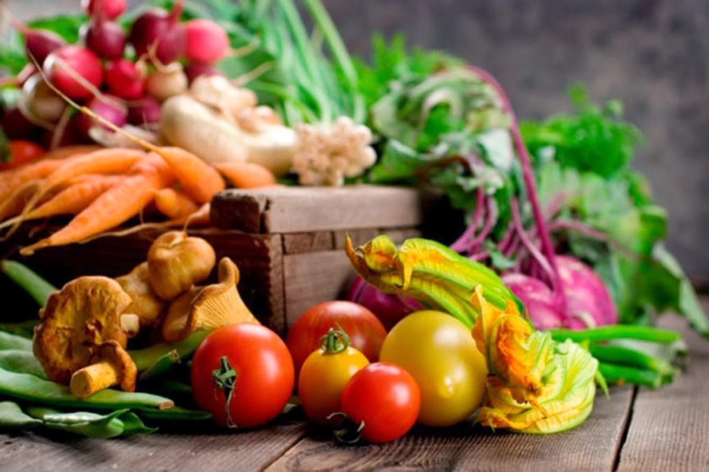 A seasonal box of vegetables on a wooden table
