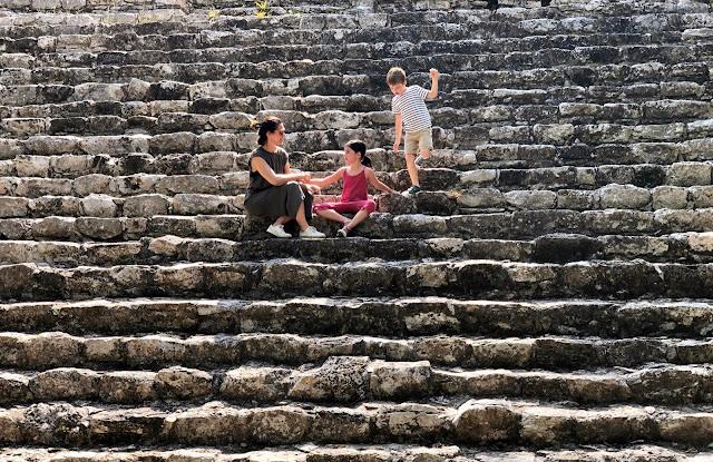 Mujer y dos niños en las escaleras de una pirámide en Cobá