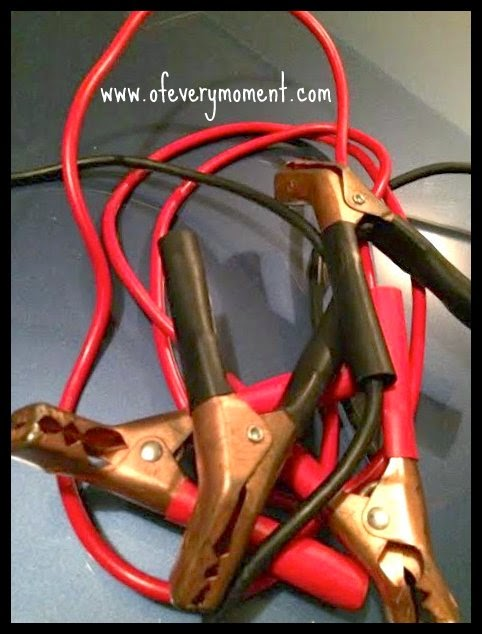 A jumble of red and black jumper cables with brass colored clamps.