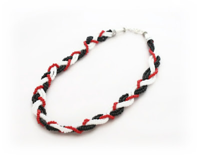 A black, white & red seed bead plaited necklace by Lottie Of London